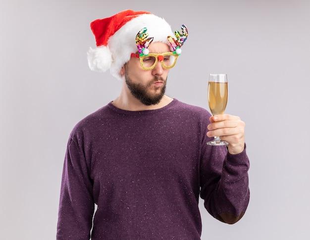 紫のセーターとサンタ帽子の若い男は、真面目な顔でそれを見て、シャンパンのガラスを保持している面白い眼鏡をかけて、白い背景の上に立っている新年の休日の概念