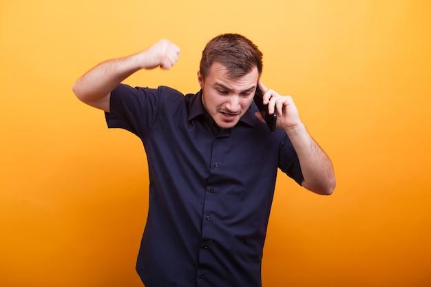黄色の背景の上に携帯電話で話している怒りの若い男。大声で叫ぶ