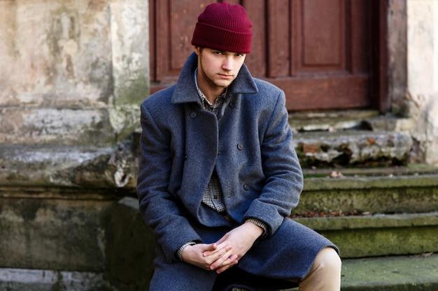 Молодой человек в красной шляпе и сером пальто сидит на разрушенных стопах