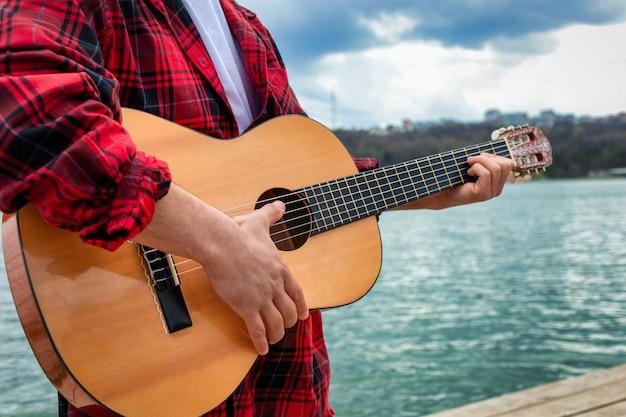 공원에서 호수 근처 기타를 연주하는 빨간색 셔츠에 젊은 남자