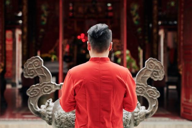 Молодой человек в красной рубашке молится у медной урны в храме, вид со спины