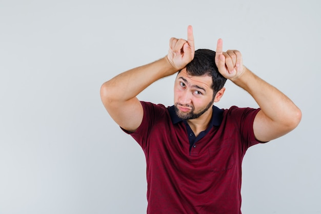 赤いtシャツを着た若い男が頭上に角のサインを示し、奇妙な正面図を示しています。