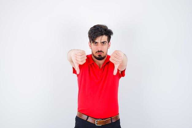 Молодой человек в красной футболке показывает большие пальцы рук обеими руками и выглядит серьезным