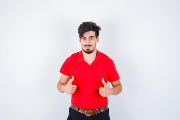 엄지 손가락을 나타나고 심각한 찾고 빨간색 티셔츠에 젊은 남자