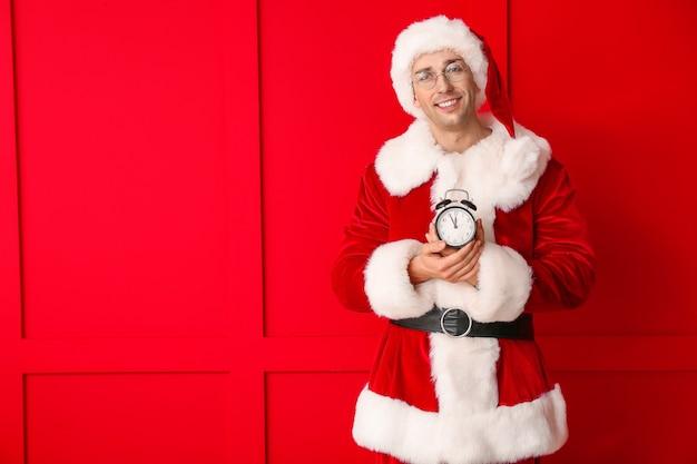 산타 의상 및 색상에 알람 시계 젊은 남자.