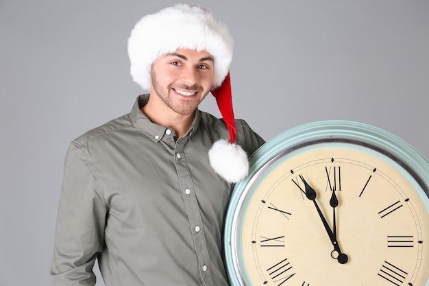 회색 벽에 시계와 산타 모자에서 젊은 남자. 크리스마스 카운트 다운 개념