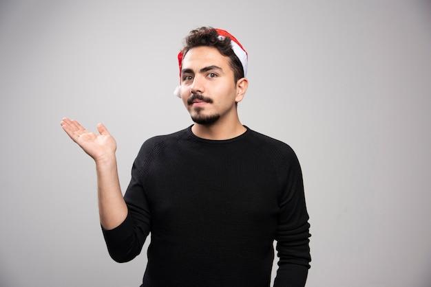 그의 팔에 보이지 않는 뭔가 들고 산타의 모자에있는 젊은 남자.