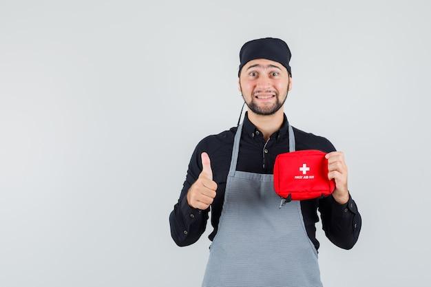 Молодой человек в рубашке, фартуке держит аптечку с большим пальцем вверх и выглядит веселым, вид спереди.