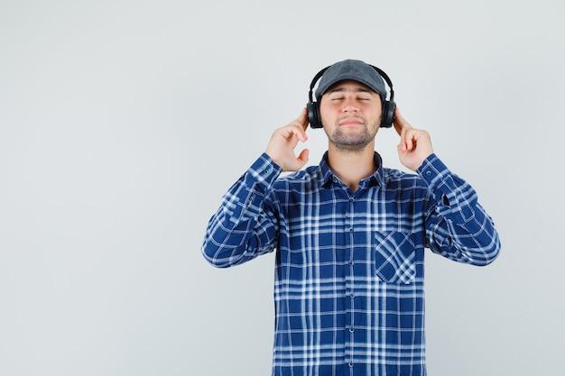 Молодой человек в рубашке, кепке, наслаждаясь музыкой в наушниках и глядя в восторге, вид спереди.