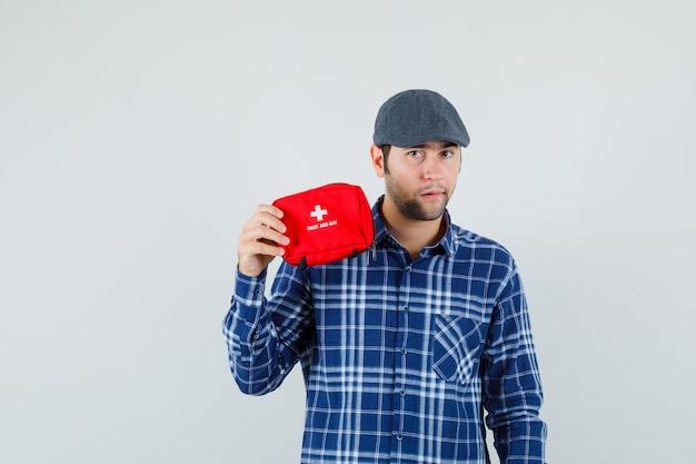 シャツを着た若い男、救急箱を保持し、自信を持って見えるキャップ、正面図。