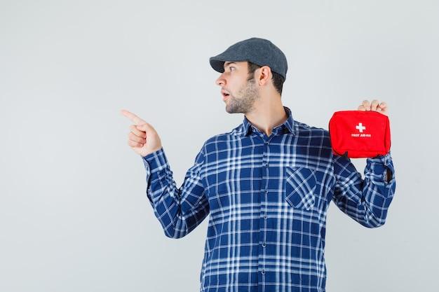 シャツを着た若い男、救急箱を保持しているキャップ、上向きに焦点を当てて見て、正面図。