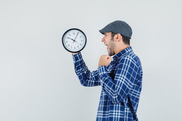 셔츠에 젊은 남자, 벽 시계를보고 행복을 찾고 모자.