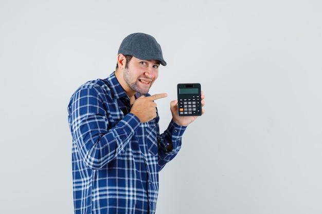 シャツを着た若い男、電卓を指して、陽気に見えるキャップ、正面図。