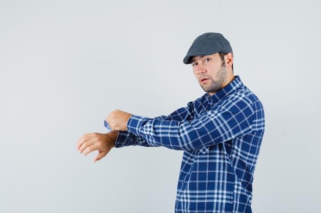 Молодой человек в рубашке, кепке закатывает рукав рубашки и выглядит уверенно, вид спереди.