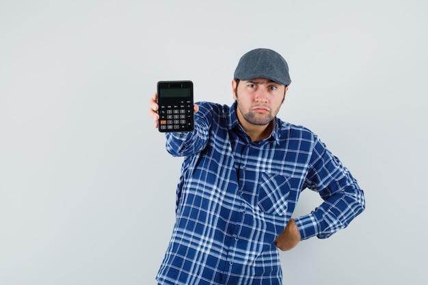 シャツを着た若い男、電卓を示し、疑わしい、正面図を示すキャップ。