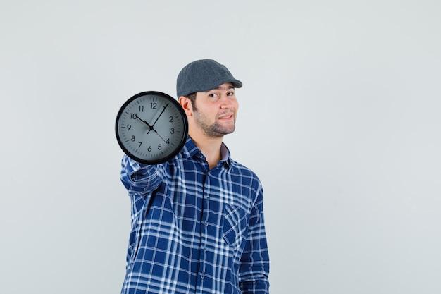 Молодой человек в рубашке, кепке показывает настенные часы и выглядит уверенно, вид спереди.