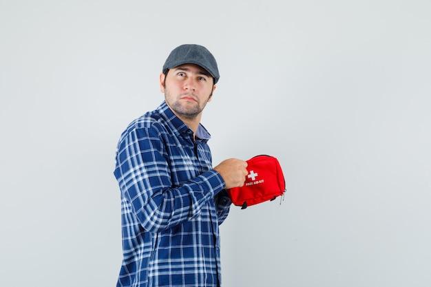 シャツを着た若い男、救急箱を開こうとしているキャップ、躊躇している、正面図。