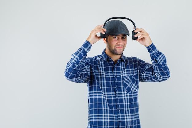 셔츠에 젊은 남자, 웃 고, 전면보기 동안 헤드폰을 착용하는 모자.