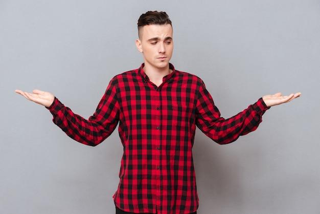 Молодой человек в рубашке выбирает между пространством на его фунтах. изолированный серый фон