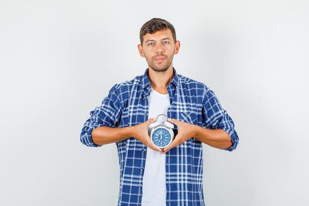 Молодой человек в рубашке держит будильник и смотрит пунктуально, вид спереди.