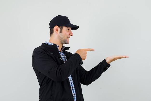 Молодой человек в рубашке, куртке, кепке, указывая на его ладонь и выглядит весело