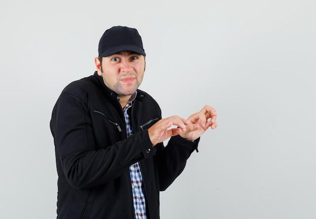 Молодой человек в рубашке, пиджаке, кепке показывает жест печати сжатыми пальцами
