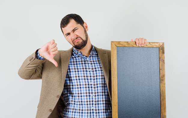 셔츠, 재킷을 들고 칠판에 젊은 남자, 아래로 엄지 손가락을 보여주는 불만족, 전면보기.
