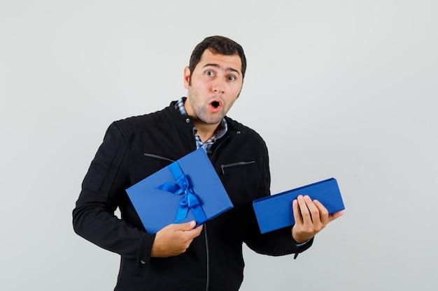 シャツを着た若い男、開いたプレゼントボックスを保持し、驚いて見えるジャケット
