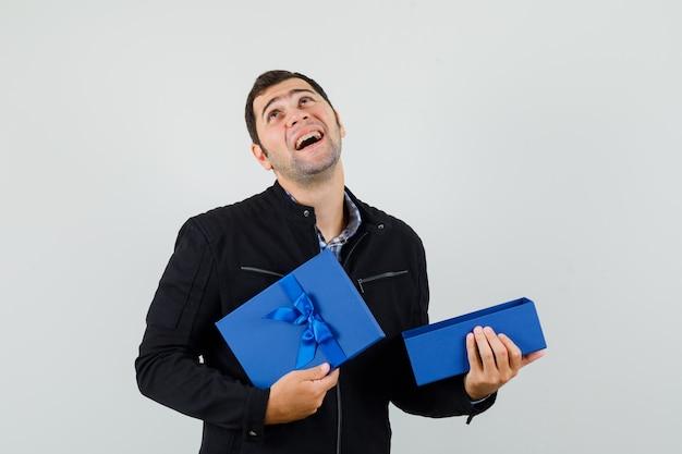 シャツを着た若い男、開いたプレゼントボックスを保持し、感謝しているジャケット