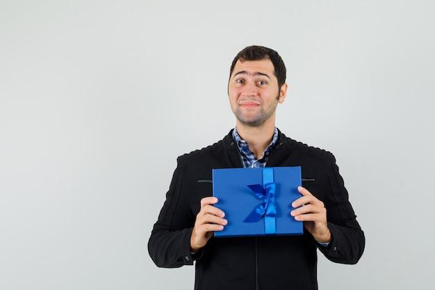 シャツを着た若い男、プレゼントボックスを保持し、陽気に見えるジャケット