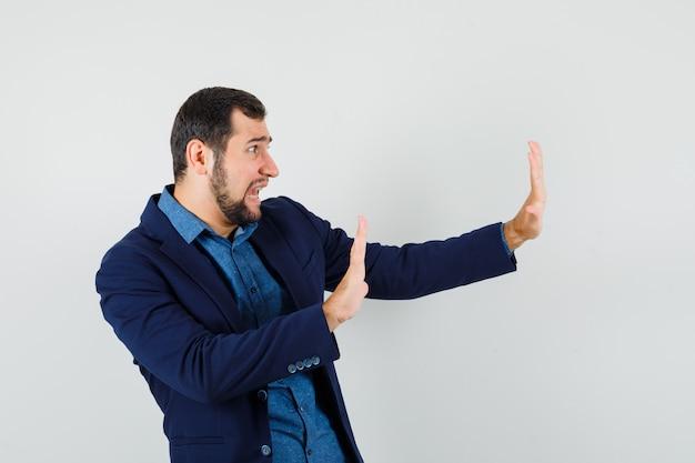 Молодой человек в рубашке, куртке держит руки в защитной манере и выглядит испуганным.