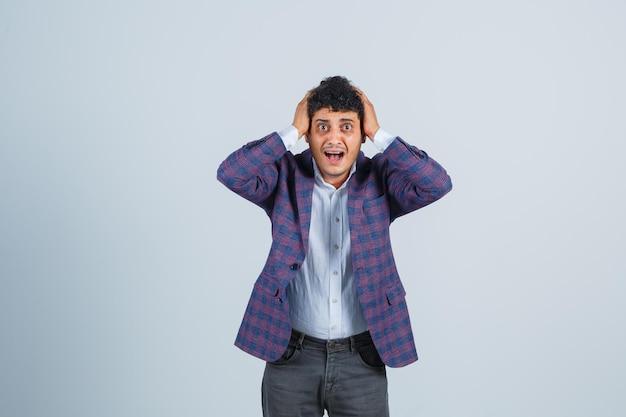 シャツ、ジャケット、ズボンを着た若い男が頭に手を置いて興奮しているように見える、正面図。