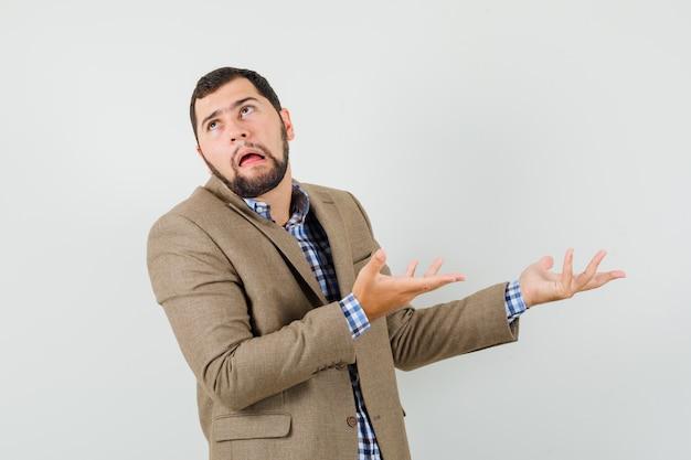 Молодой человек в рубашке, куртке с презрением и высокомерным видом, вид спереди.