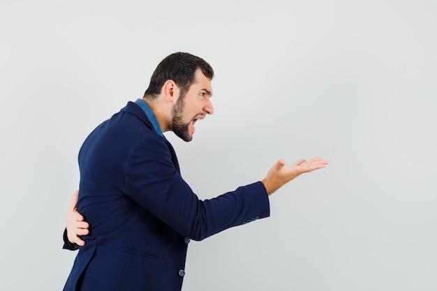 Молодой человек в рубашке, куртке кричит на кого-то и выглядит сердитым.