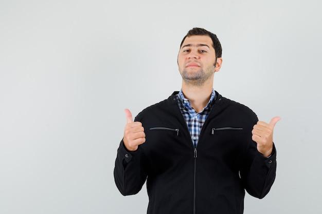 Молодой человек в рубашке, куртке показывает двойные пальцы вверх и выглядит уверенно