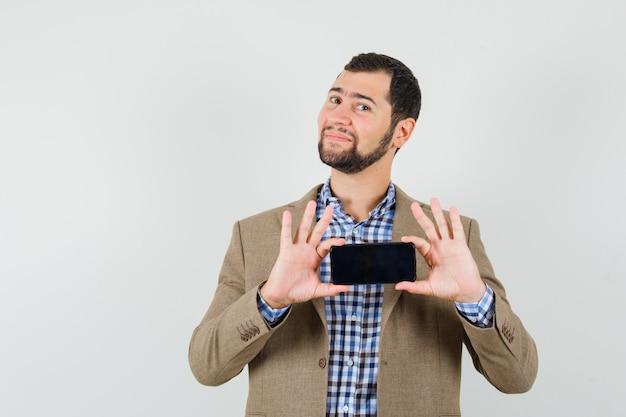 셔츠에 젊은 남자, 재킷 휴대 전화에 사진을 찍고 기쁜 찾고
