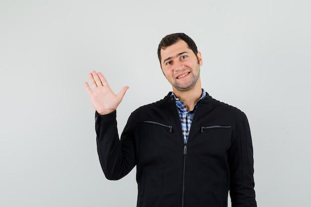 Молодой человек в рубашке, куртке машет рукой, чтобы попрощаться и выглядит веселым