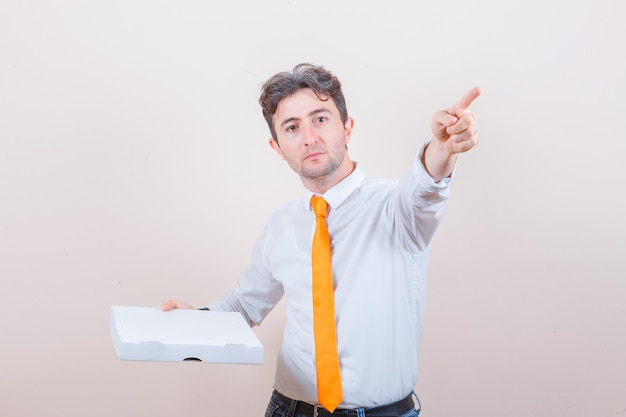 셔츠, 청바지 피자 상자를 들고, 멀리 가리키는 젊은 남자