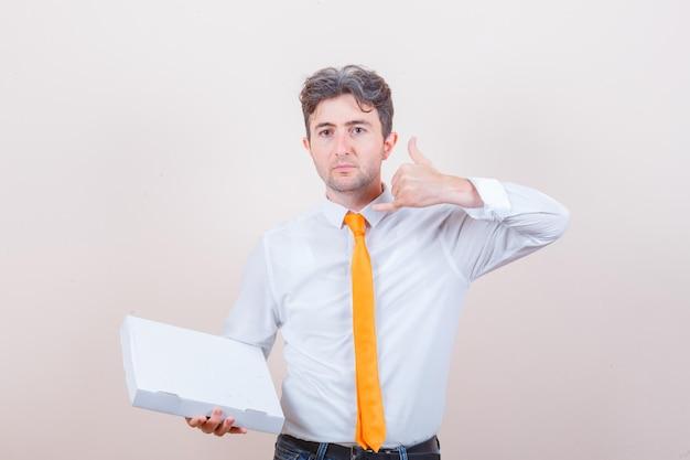 셔츠, 청바지 피자 상자를 들고, 전화 제스처를 보여주는 젊은 남자
