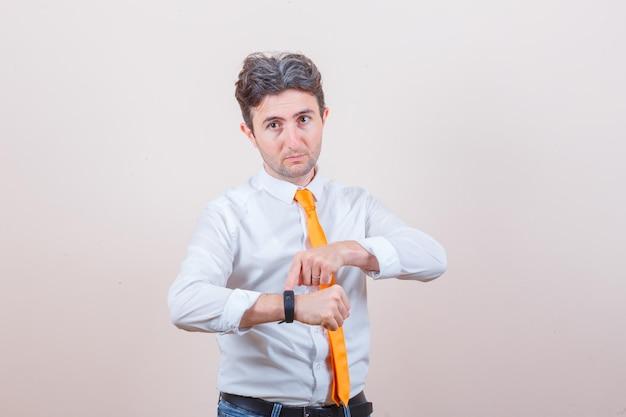셔츠에 젊은 남자, 그의 스마트 워치를 가리키고 시간을 지키는 청바지