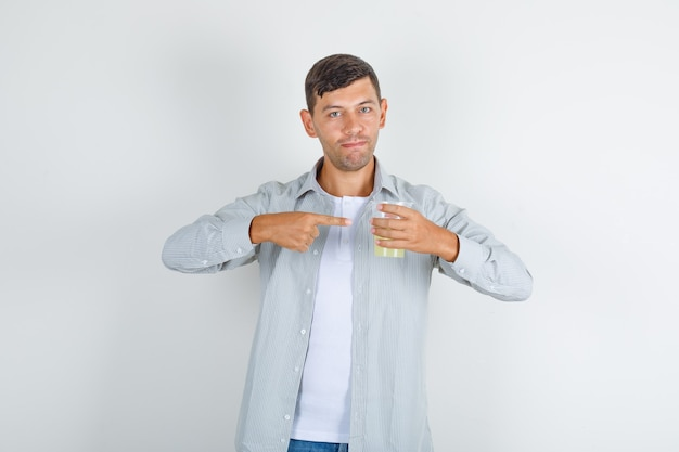 シャツ、ジーンズの指でジュースのガラスを示す若い男