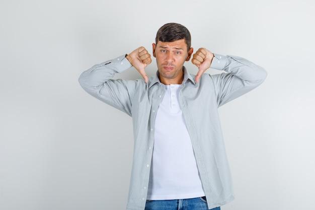 若い男のシャツ、ジーンズを親指を表示して悲しい探して