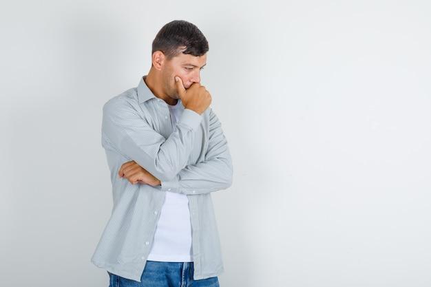 Молодой человек в рубашке, джинсах думает, положив руку на подбородок