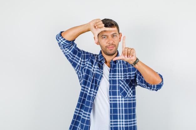 フレームジェスチャーを作成し、自信を持って見えるシャツの若い男、正面図。