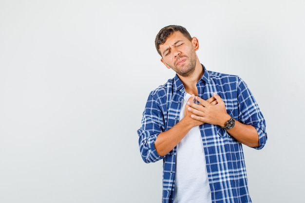 胸に手を当てて感謝のジェスチャーをし、感謝の気持ちを表すシャツを着た若い男、正面図。
