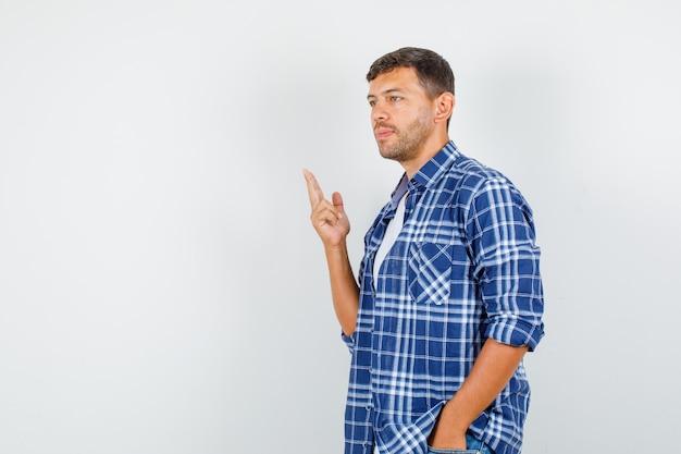 Молодой человек в рубашке делает жест стрельбы из пистолета и выглядит задумчивым, вид спереди.