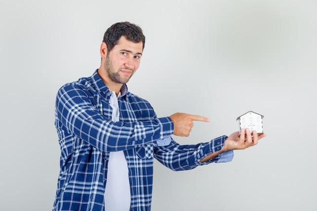 家のモデルで指を指して、希望に満ちてシャツの若い男