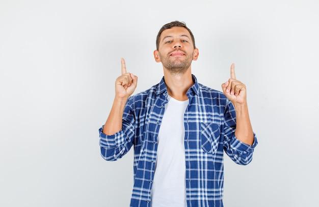 Молодой человек в рубашке, указывая пальцами вверх с закрытыми глазами и уверенно глядя, вид спереди.