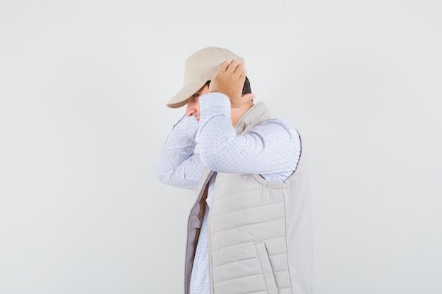 シャツ、ノースリーブのジャケット、耳に手をつないでキャップの若い男。