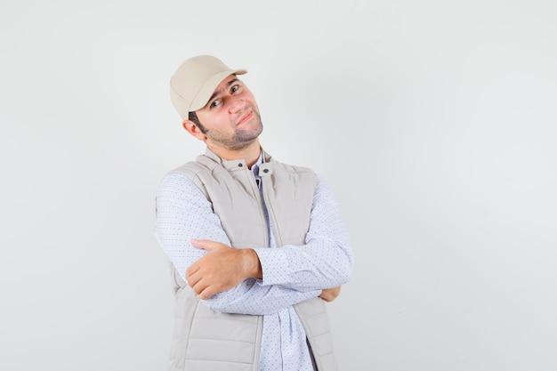 シャツを着た若い男、ノースリーブのジャケット、腕を組んで立っているキャップ、満足そうに見える、正面図。